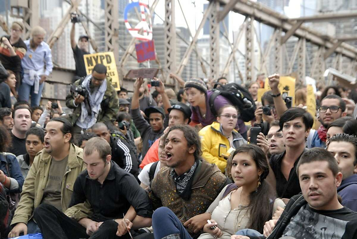 In this Oct. 1, 2011 photo, protesters sit with arms linked on New York's Brooklyn Bridge before police began making arrests during Saturday's march by Occupy Wall Street. Protesters speaking out against corporate greed and other grievances attempted to walk over the bridge from Manhattan, resulting in the arrest of more than 700 during a tense confrontation with police. The majority of those arrested were given citations for disorderly conduct and were released, police said. (AP Photo/Stephanie Keith)