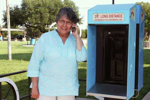 Stopping at an abandoned pay phone, Minnie Mims uses her cellphone on Interstate 10 in West Texas.  Photo: Forrest Mims III, For The Express-News