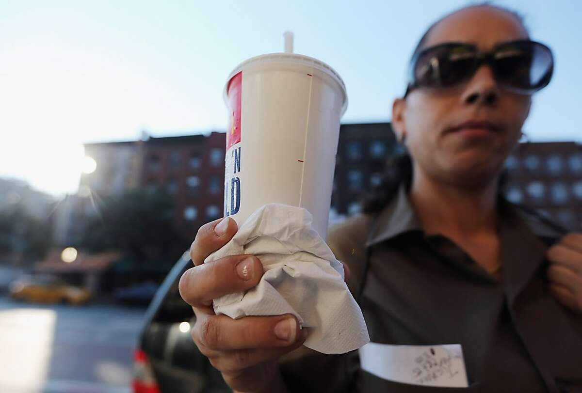 """NEW YORK, NY - SEPTEMBER 13: Jasmine Batista displays a 21-ounce soda she purchased at McDonalds in Manhattan after the New York City Board of Health voted to ban the sale of large sugary drinks at restaurants and concessions on September 13, 2012 in New York City. Batista said once the ban goes in effect she will purchase 2-liter soda bottles from businesses that aren't affected by the ban. Batista said, """"I can't stand people telling me what I can drink."""" The controversial measure bars the sale of sugar drinks larger than 16 ounces in an effort to combat obesity. (Photo by Mario Tama/Getty Images)"""