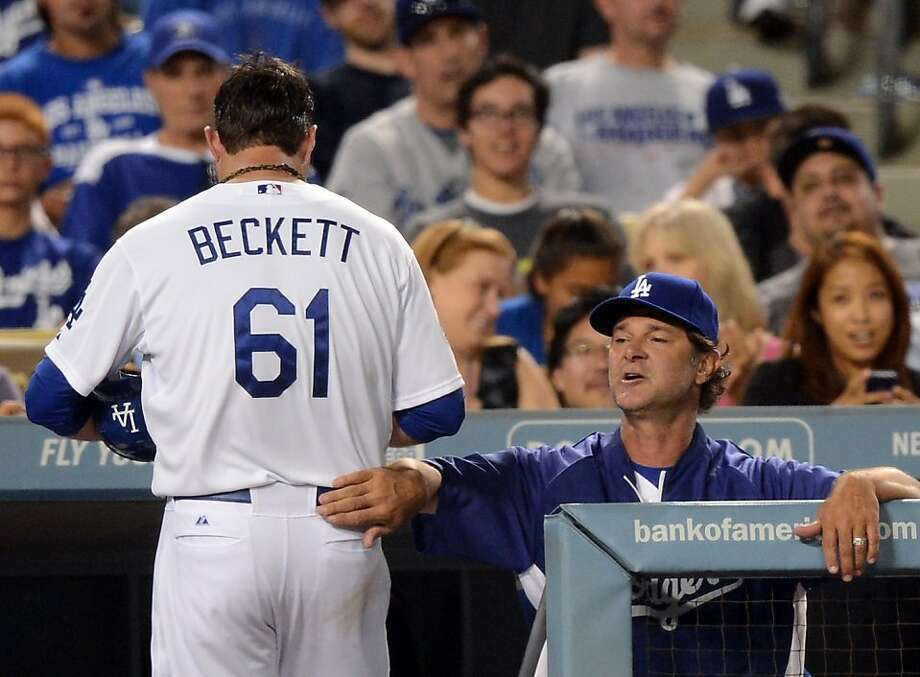 Manager Don Mattingly pats Josh Beckett after the pitcher was thrown out at first when he didn't hustle on a liner to right, a defining play for the Dodgers. Photo: Harry How, Getty Images
