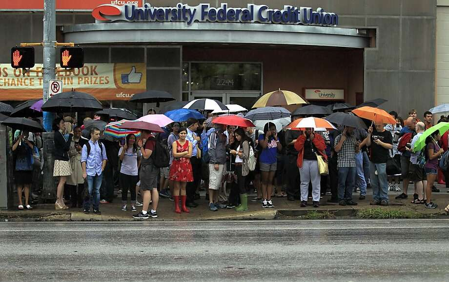The University of Texas sent a safety alert text message warning of a threat on campus, forcing students to evacuate the buildings and stand in the rain. Photo: Ricardo B.Brazziell, Associated Press