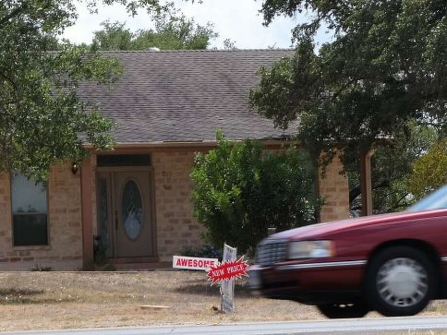 A car drives by a home for sale on Evans Road just east of Bulverde Road on Wednesday, Sept. 12, 2012. (San Antonio Express News)