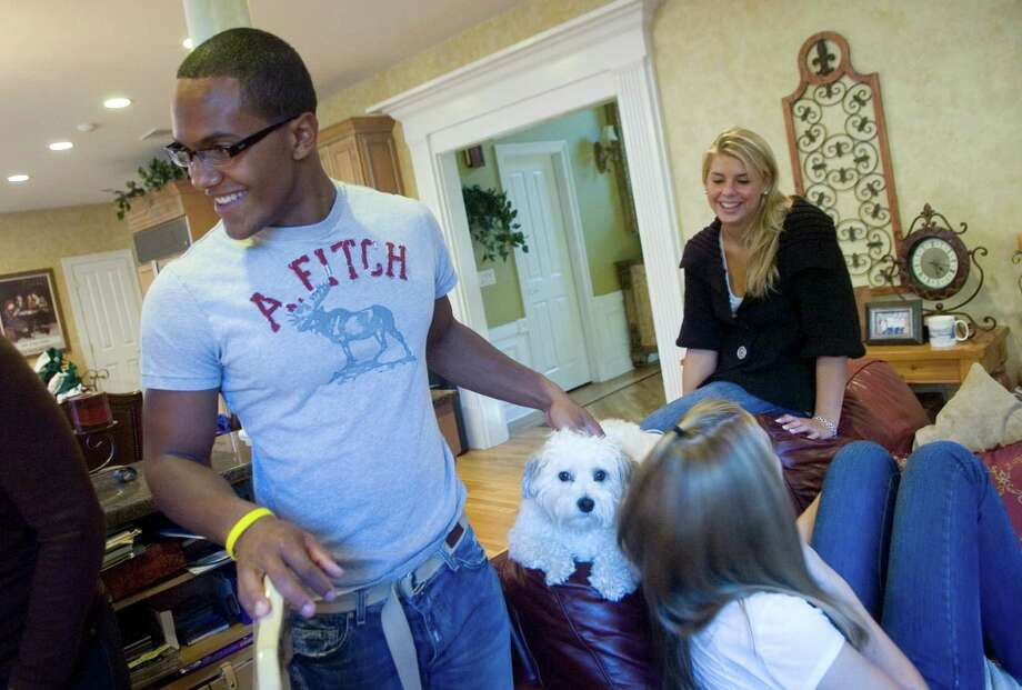 Marcus Dixon spends a Sunday afternoon at home with two of his three sisters, Lauren McInerney, 17 (on end of couch), and Kelley McInerney, 13. Photo: Kathleen O'Rourke/filephoto / Stamford Advocate