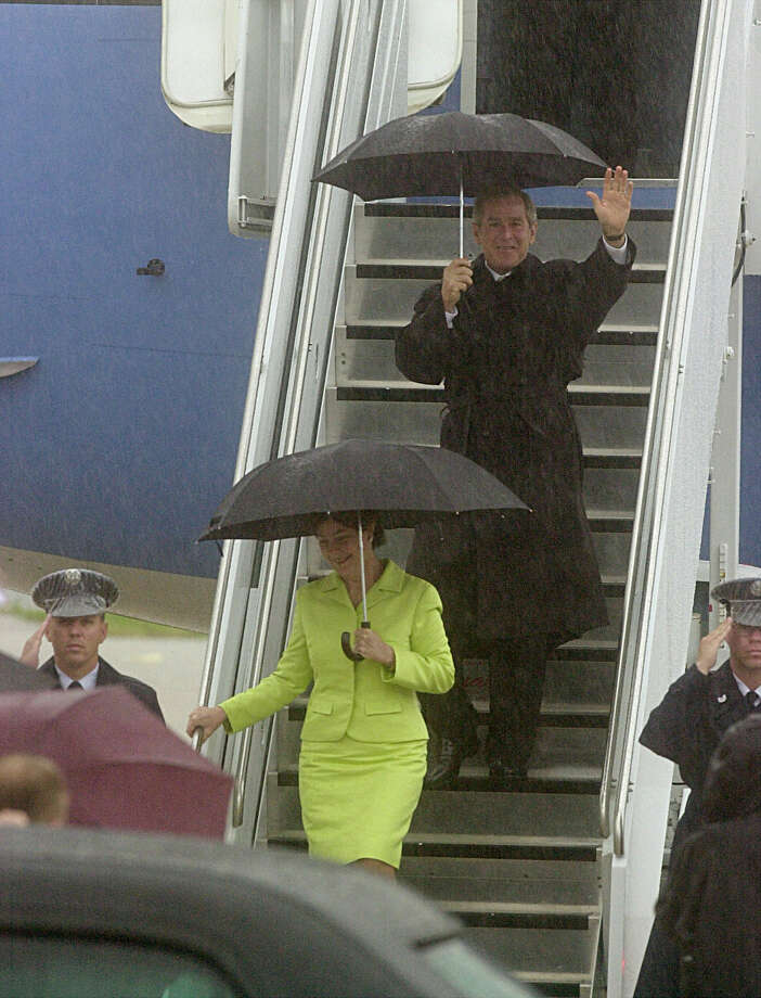 Rain pours down as President George W. Bush and First Lady Laura Bush wave to the crowd while exiting Air Force One at the Ratheon Hanger in San Antonio on Wednesday, Aug. 29, 2001. Photo: Delcia Lopez, San Antonio Express-News File Photo / SAN ANTONIO EXPRESS NEWS