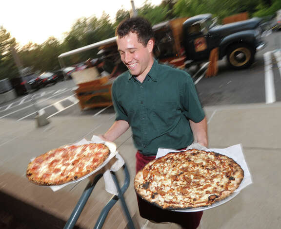 "Erik Coffin-Gould of Big Green Truck Pizza of New Haven delivers two wood fired brick oven pizzas to the Community Answers Inc. fundraiser ""Comedy Night @ the Cole,"" at Greenwich Library, Friday, Sept. 14, 2012. Housed at Greenwich Library, Community Answers is an independent nonprofit information and referral service that is part of the United Way Agency that provides answers to a wide variety of questions of interest to the Greenwich community. Photo: Bob Luckey / Greenwich Time"