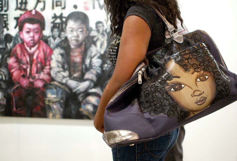 "With the image of a child on her purse, Dionne Green of Houston, looks at a painting by Tianbing Li titled ""Sitting In Front of Propaganda"" in the Galerie Kashya Hildebrand exhibit booth during the Houston Fine Art Fair in Reliant Center Friday, Sept. 14, 2012, in Houston. Photo: Johnny Hanson, Houston Chronicle / © 2012  Houston Chronicle"