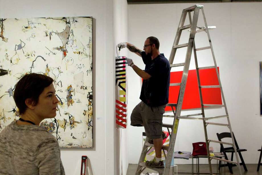 Artist Jonathan Leach, right, hangs one of his pieces of art as Ariane Roesch looks on in the Gallery Sonja Roesch exhibit booth at the Houston Fine Art Fair in Reliant Center Friday, Sept. 14, 2012, in Houston. Photo: Johnny Hanson, Houston Chronicle / © 2012  Houston Chronicle