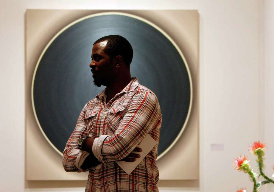 "Local artist Kevin Thomas stands in front of a painting by Robert Schaberl titled ""ZF Dark Petrol with Dark Magenta"" in the Galerie Kashya Hildebrand exhibit booth during the Houston Fine Art Fair in Reliant Center Friday, Sept. 14, 2012, in Houston. ""It's refreshing to see everybody's blessings,"" Thomas said. Photo: Johnny Hanson, Houston Chronicle / © 2012  Houston Chronicle"