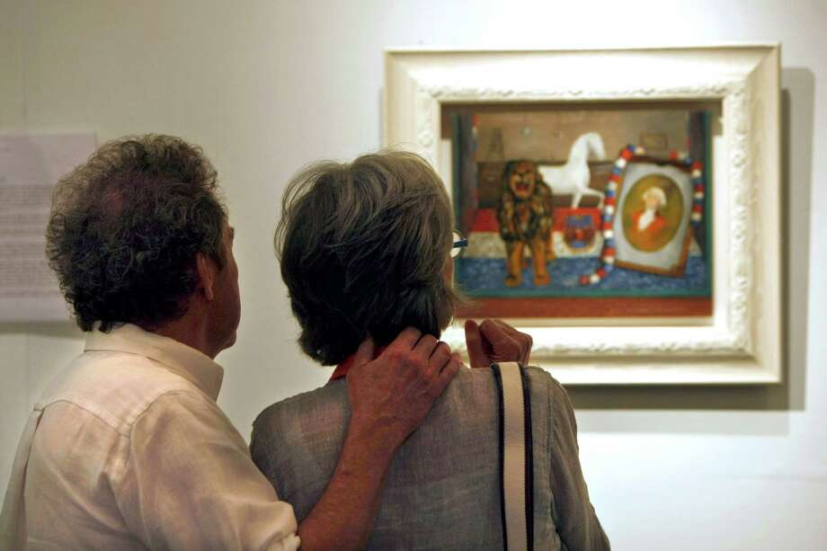 "Gary and Jane Swanson look at at Frida Kahlo painting titled ""Display Window in a Street of Detroit, 1931"" valued at $2 million in the Cernuda Arte exhibit area at the Houston Fine Art Fair. Photo: Johnny Hanson, Houston Chronicle / © 2012  Houston Chronicle"