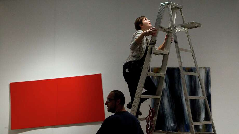 Next to artist Jonathan Leach, left, Ariane Roesch climbs a ladder to adjust the lighting in the Gallery Sonja Roesch exhibit booth at the Houston Fine Art Fair in Reliant Center Friday, Sept. 14, 2012, in Houston. Photo: Johnny Hanson, Houston Chronicle / © 2012  Houston Chronicle