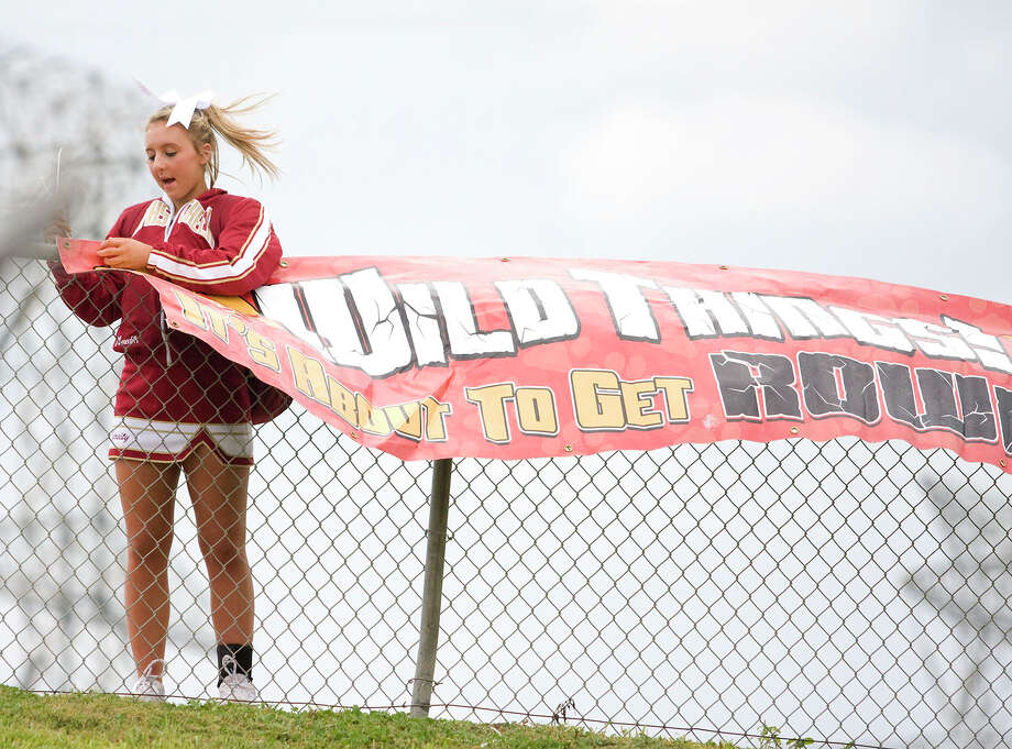 Cy Woods cheerleader has trouble hanging spirit signs as weather moves in before the Cy Woods Homecoming game against Langham Creek at Pridgeon Stadium on Friday, Sept. 14, 2012, in Houston. Photo: Joe Buvid, For The Chronicle / © 2012 Joe Buvid