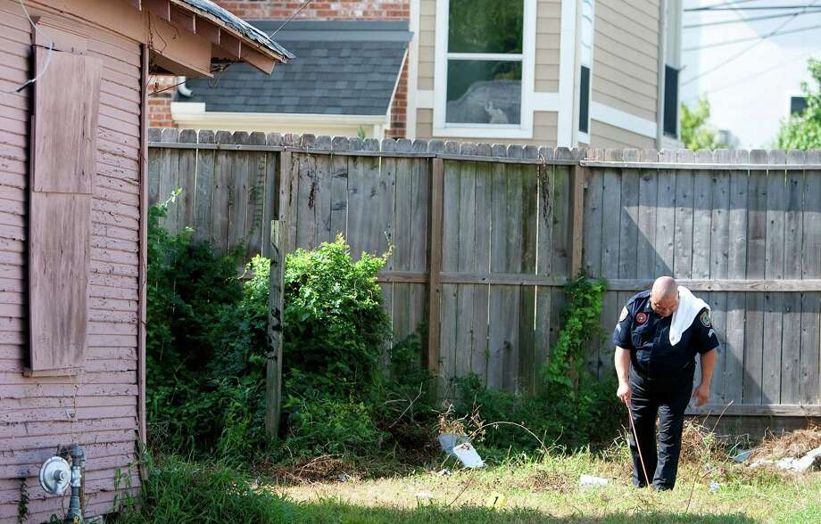 A police officer investigates Friday after a melee on Nagle Street. Police shot and killed a knife-wielding suspect after he stabbed three people and then charged officers outside the southeast Houston home. Photo: Cody Duty / © 2012 Houston Chronicle