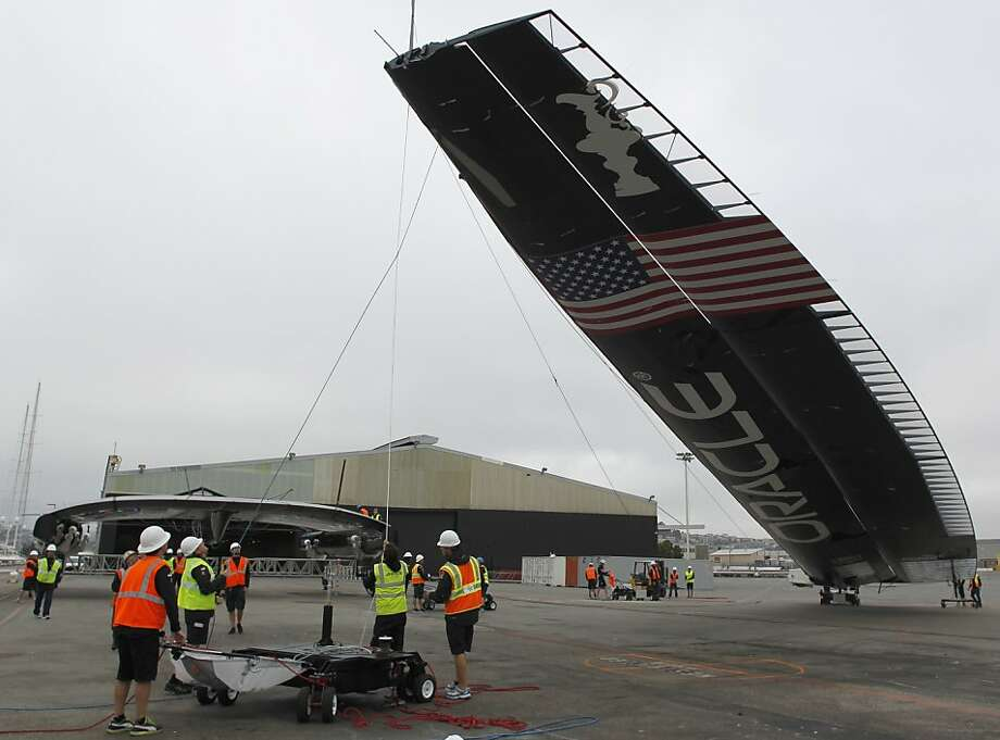 Technicians remove the 131-foot-tall wing of Team Oracle's AC72 America's Cup catamaran. Photo: Paul Chinn, The Chronicle