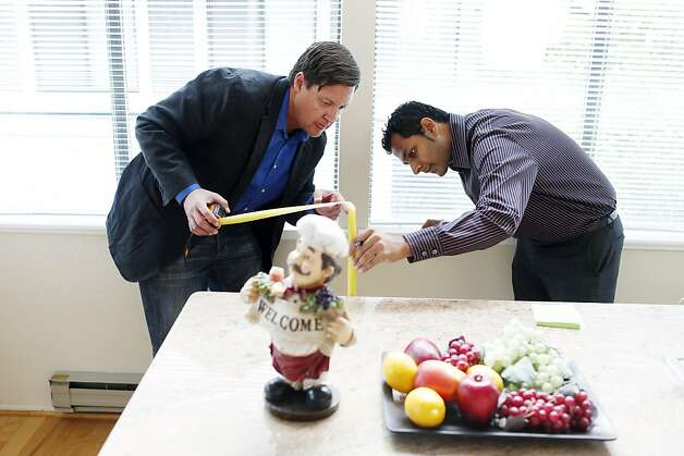 Maurice Sandoval (left), an agent with Redfin, helps client Akil Murali of Palo Alto take measurements at a home Murali is buying in Foster City. The Bay Area market saw strong signs of a rebound in August. Photo: Beck Diefenbach, Special To The Chronicle