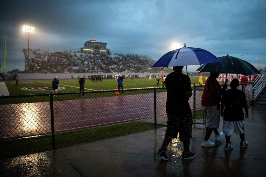 Fans take cover as rain drenches the stadium during the first quarter of a high school football game between Pearland and Memorial at The Rig on Friday, Sept. 14, 2012, in Pearland. Photo: Smiley N. Pool, Houston Chronicle / © 2012  Houston Chronicle