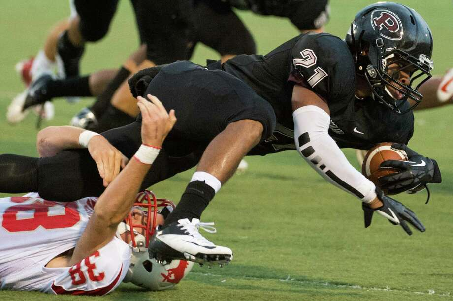 Pearland's Devante Dotson (21) is brought down by Memorial's Griffin Doyle (38) during the first quarter of a high school football game against Memorial at The Rig on Friday, Sept. 14, 2012, in Pearland. Photo: Smiley N. Pool, Houston Chronicle / © 2012  Houston Chronicle