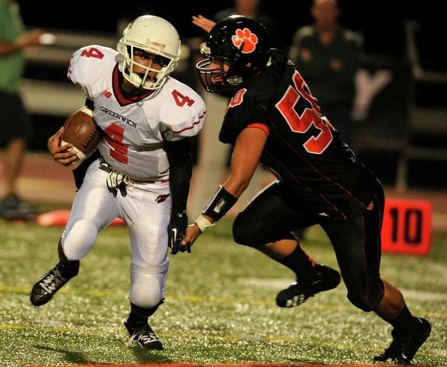 Greenwich's Jose Melo scrambles while under pressure from Ridgefield's Andrew Barton during their game at Ridgefield High School on Friday, Sept. 14, 2012. Photo: Jason Rearick / The News-Times