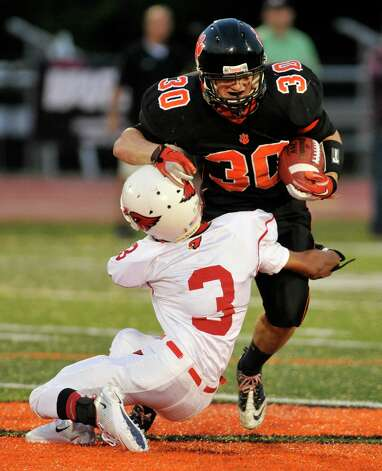 Ridgefield's Sam Gravitte runs into Greenwich's Austin Longi during their game at Ridgefield High School on Friday, Sept. 14, 2012. Photo: Jason Rearick / The News-Times