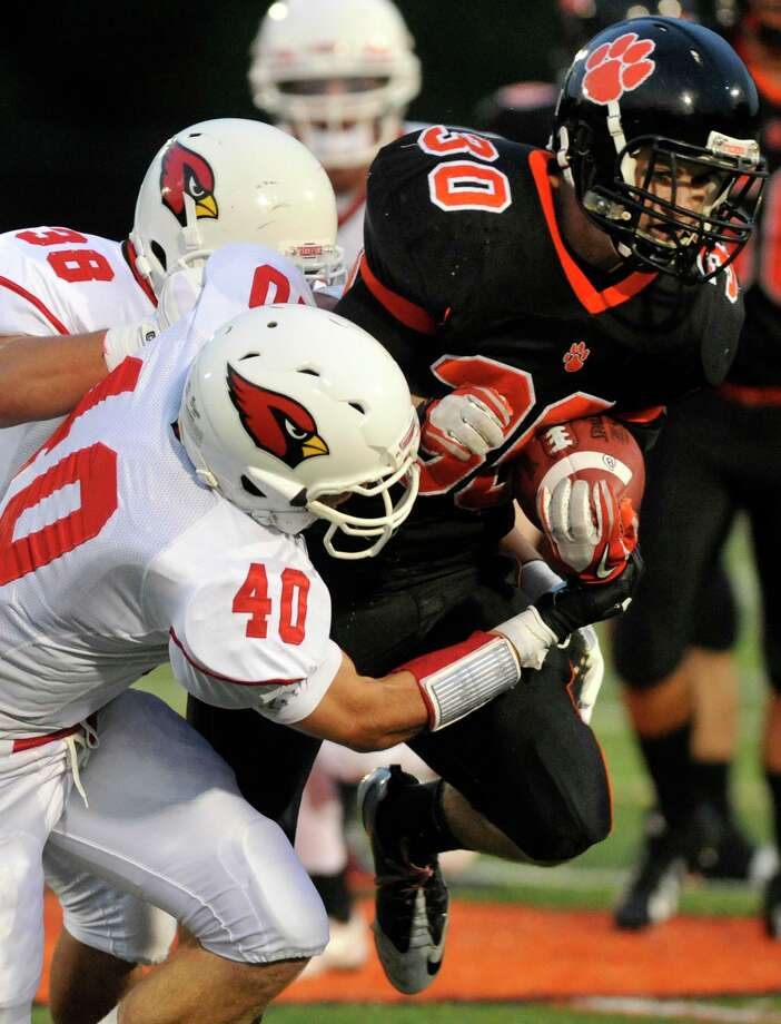 Ridgefield's Sam Gravitte is tackled by Greenwich's Taylor Olmstead(40) and Dan Claroni during their game at Ridgefield High School on Friday, Sept. 14, 2012. Photo: Jason Rearick / The News-Times