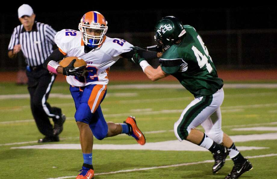 Danbury's Tysheen McCrea moves the ball as Norwalk's James McInerney closes in as Norwalk High School hosts Danbury in a football game Friday, Sept. 14, 2012. Photo: Keelin Daly / Stamford Advocate Freelance