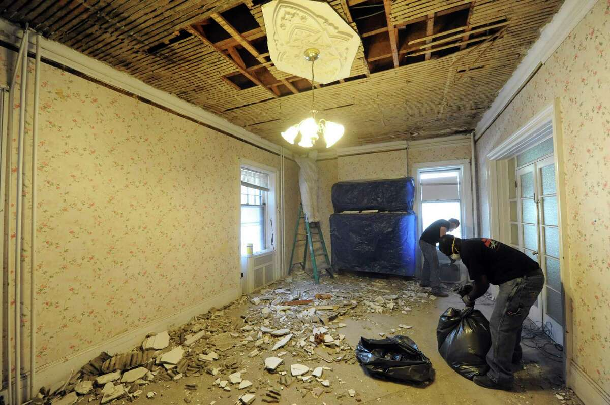 Quick Response crews clear damaged plaster at Mercy House, a 19-bed emergency shelter for women run by the Catholic Charities Housing Office, after it flooded on Saturday when the drainage system on the building?s flat roof could no longer handle the downpour in Albany, NY Friday Sept. 14, 2012. (Michael P. Farrell/Times Union)