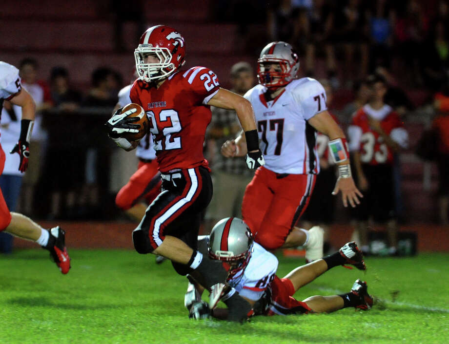 Masuk's #22 Thomas Milone evades a tackle attempt by Pomperaug's #89 Michael Buntin, to carry the ball all the way to the endzone for a touchdown, during boys football action in Monroe, Conn. on Friday September 14, 2012. Photo: Christian Abraham / Connecticut Post