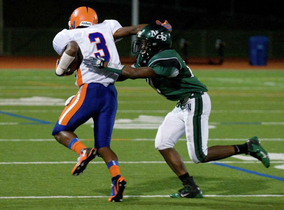 Norwalk's Hopeton Chambers closes in on Danbury's Corey Acosta as Norwalk High School hosts Danbury in a football game Friday, Sept. 14, 2012. Photo: Keelin Daly / Stamford Advocate Freelance