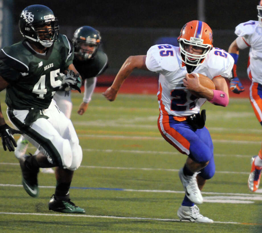 Danbury's Kolyn Danzy moves the ball as Norwalk's Jonathan Torres-Wills closes in as Norwalk High School hosts Danbury in a football game Friday, Sept. 14, 2012. Photo: Keelin Daly / Stamford Advocate Freelance