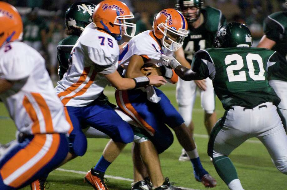 DAnbury quarterback Anferny Ith pushes for yards with some help from teammate Jacob Reich, left, as Norwalk's Andre Cork closes inNorwalk High School hosts Danbury in a football game Friday, Sept. 14, 2012. Photo: Keelin Daly / Stamford Advocate Freelance
