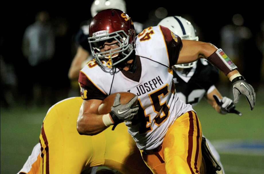 St. Joseph's Mike Pulaski carries the ball during Friday's game at Staples High School in Westport on September 14, 2012. Photo: Lindsay Niegelberg / Stamford Advocate