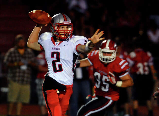 Pomperaug QB Eric Beatty gets ready to pass the ball as Masuk's #35 Tyler Camp comes in from behind looking for a sack, during boys football action in Monroe, Conn. on Friday September 14, 2012. Photo: Christian Abraham / Connecticut Post