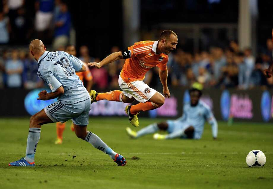 KANSAS CITY, KS - SEPTEMBER 14:  Brad Davis #11 of Houston Dynamo is tripped up by Aurelien Collin #78 of Sporting KC during the MLS game at Livestrong Sporting Park on September 14, 2012 in Kansas City, Kansas. Photo: Jamie Squire, Getty Images / 2012 Getty Images