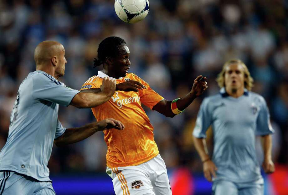 KANSAS CITY, KS - SEPTEMBER 14:  Macoumba Kandji #9 of Houston Dynamo battles Aurelien Collin #78 of Sporting KC for the ball during the MLS game at Livestrong Sporting Park on September 14, 2012 in Kansas City, Kansas. Photo: Jamie Squire, Getty Images / 2012 Getty Images