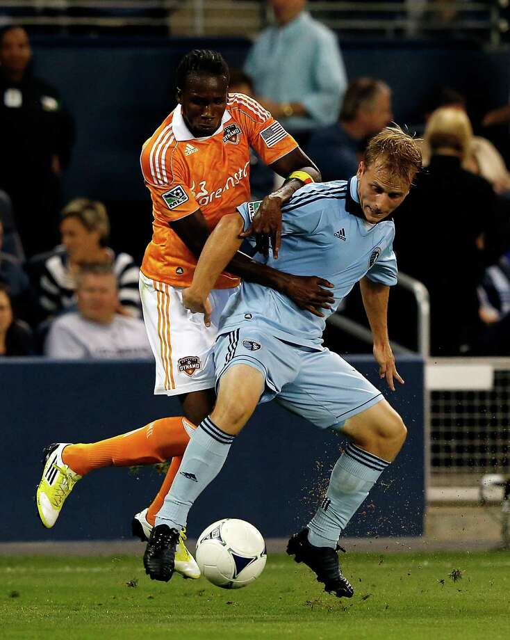 KANSAS CITY, KS - SEPTEMBER 14:  Macoumba Kandji #9 of Houston Dynamo battles Seth Sinovic #16 of Sporting KC for the ball during the MLS game at Livestrong Sporting Park on September 14, 2012 in Kansas City, Kansas. Photo: Jamie Squire, Getty Images / 2012 Getty Images