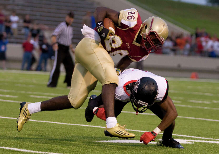 Cy Woods running back Egbezien Obiomon (26) is tackled by Isreal Giles (9) of Langham Creek after rushing for a short gain on the opening possesion on the game against Langham Creek at Pridgeon Stadium on Friday, Sept. 14, 2012, in Houston. Photo: Joe Buvid, For The Chronicle / © 2012 Joe Buvid