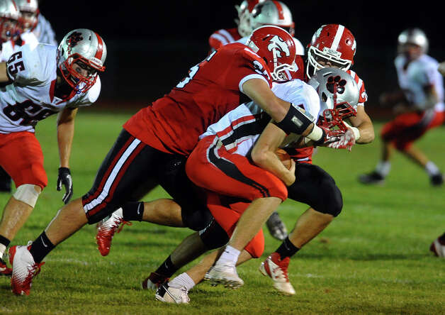 Pomperaug QB Eric Beatty gets sacked by Masuk players, during boys football action in Monroe, Conn. on Friday September 14, 2012. Photo: Christian Abraham / Connecticut Post