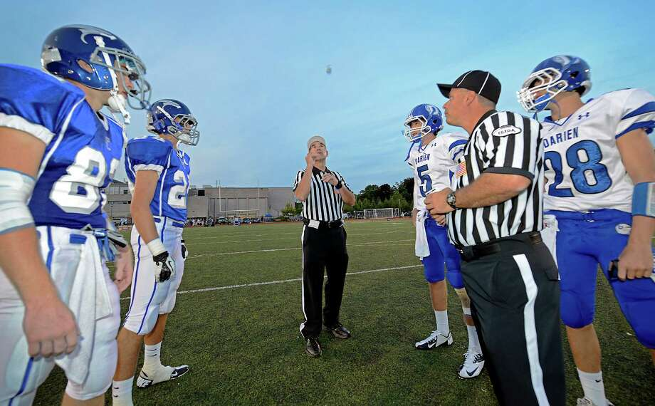 Team captains for both the Darien high school and Fairfield Ludlowe high school football teams watch the referee's coin toss at the start of the season opening football game held at Fairfield Ludlowe high school, Fairfield, CT on Friday September 14th 2012 Photo: Mark Conrad / Connecticut Post Freelance
