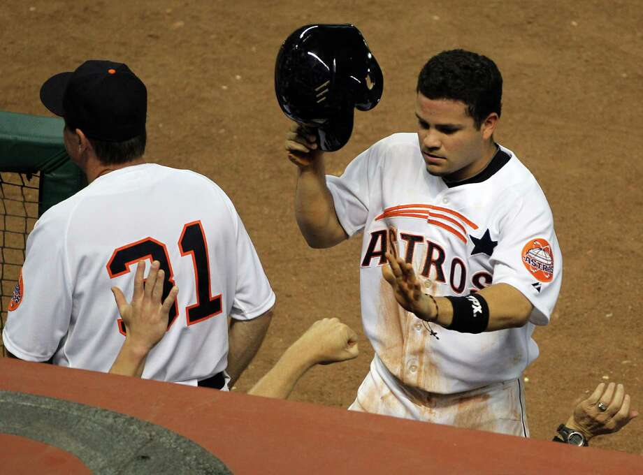 May 18: Rangers 4, Astros 1Jose Altuve (27) is greeted with a assortment of hands in the dugout after scoring a run during the third inning. The Astros hardly came close to scoring after that.Record: 17-22. Photo: Nick De La Torre, Houston Chronicle / © 2012  Houston Chronicle