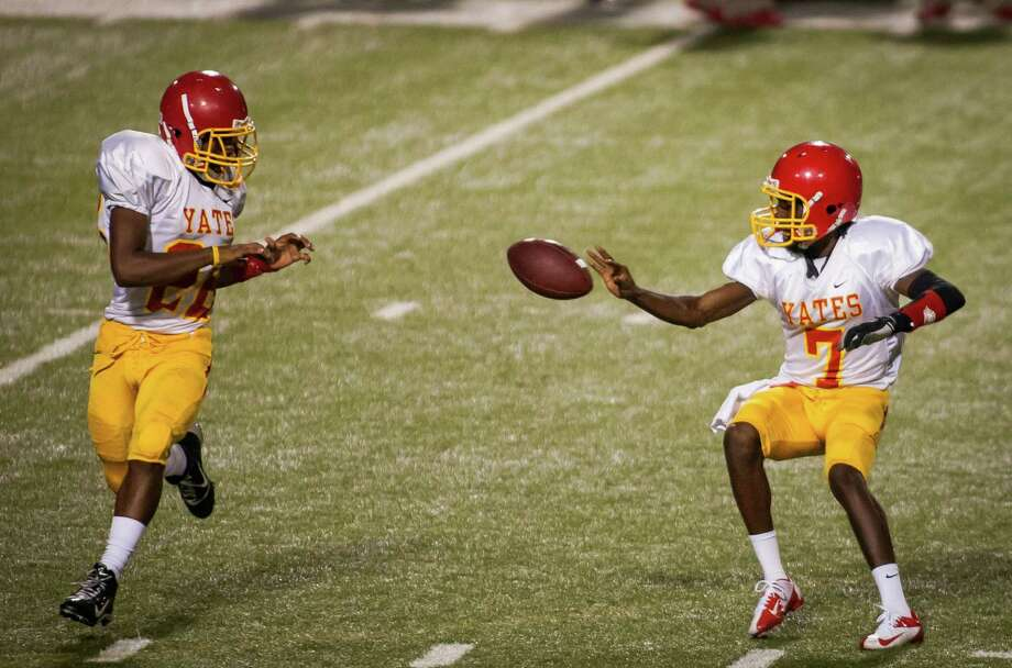 Yates quarterback Joshua Simmons (7) pitches the ball to Khalil Wagner (22) during the third quarter of a high school football game at Barnett Stadium on Friday, Sept. 14, 2012, in Houston. Madison defeated Yates 35-0. Photo: Andrew Richardson, For The Chronicle / © 2012 Andrew Richardson