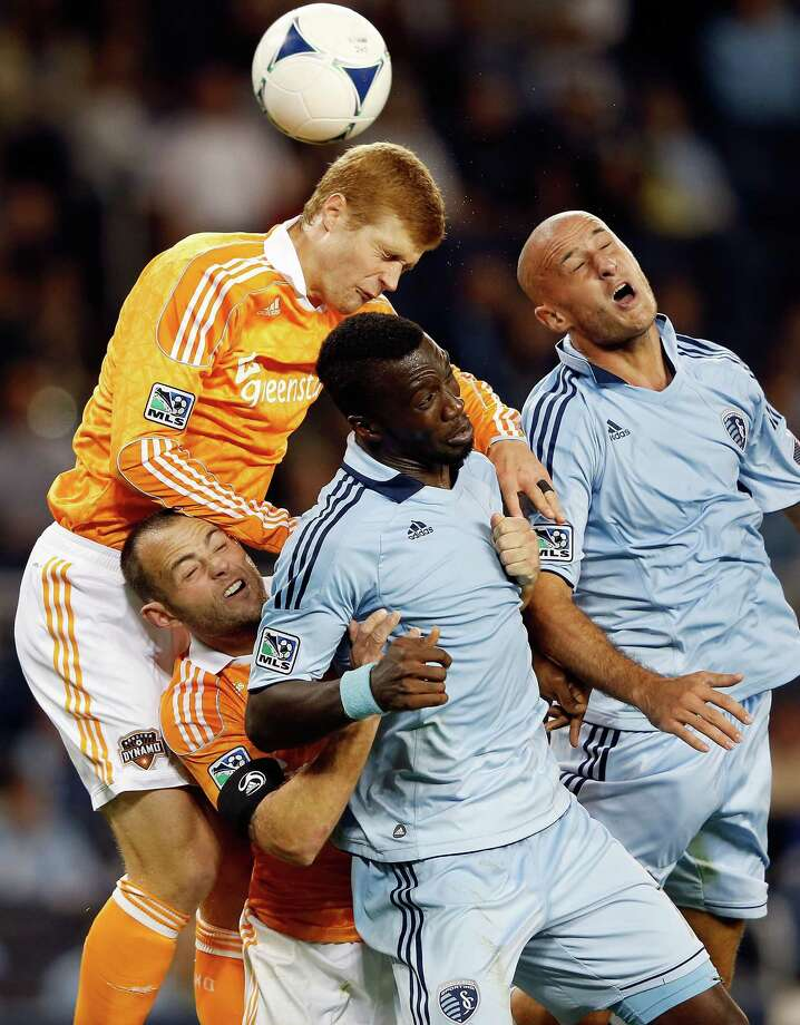 KANSAS CITY, KS - SEPTEMBER 14:  Andre Hainault #31 of the Houston Dynamo battles Brad Davis #11, C.J. Sapong #17, and Aurelien Collin #78 of Sporting KC for a header during the MLS game at Livestrong Sporting Park on September 14, 2012 in Kansas City, Kansas. Photo: Jamie Squire, Getty Images / 2012 Getty Images