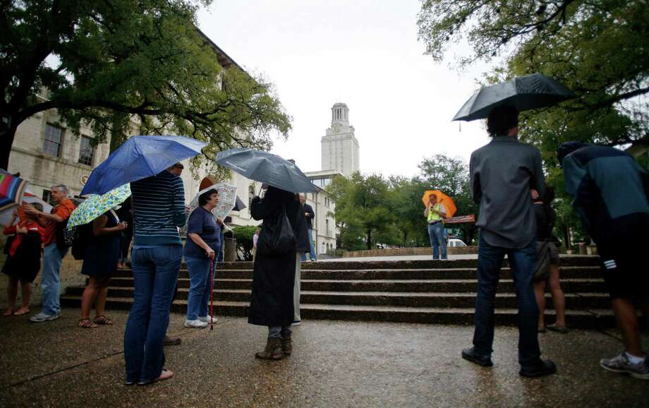 University  of Texas  students, staff and faculty found  themselves with little to do but wait   after being evacuated from campus buildings Friday. Photo: Thao Nguyen / FR159307 AP