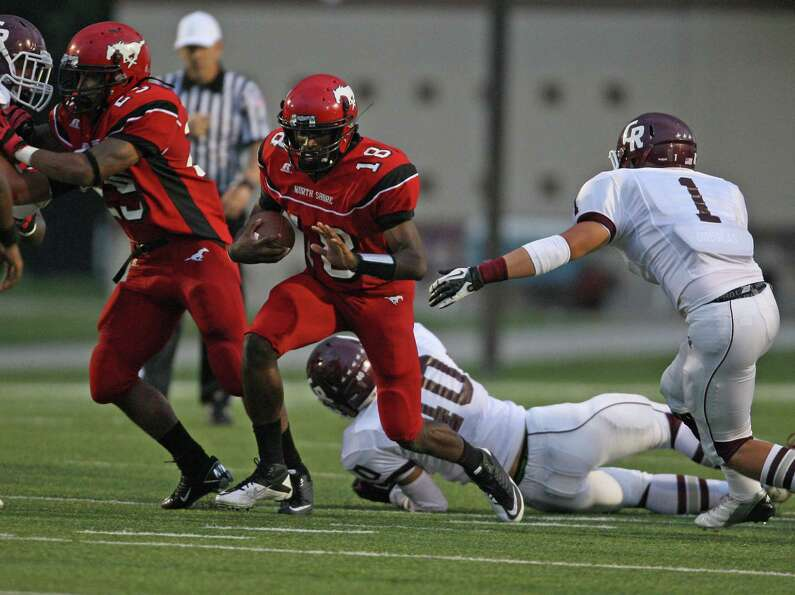 North Shore quarterback Micah Thomas (18) escapes the tackles of Cinco Ranch's Andy Chan (40) and Be