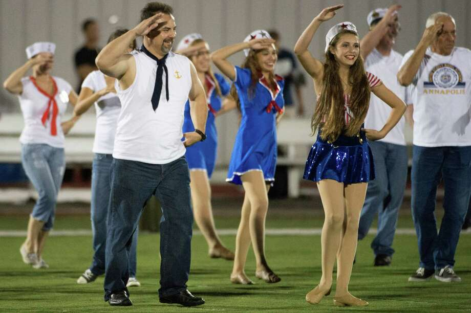 Alex Pena, left, performs in a dance routine with his daughter Celina, right, as parents join the Pearland Prancers drill team halftime show during a high school football game against Memorial at The Rig on Friday, Sept. 14, 2012, in Pearland. Photo: Smiley N. Pool, Houston Chronicle / © 2012  Houston Chronicle