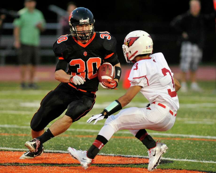 Ridgefield's Sam Gravitte evades Greenwich's Austin Longi during their game at Ridgefield High School on Friday, Sept. 14, 2012. Photo: Jason Rearick / The News-Times