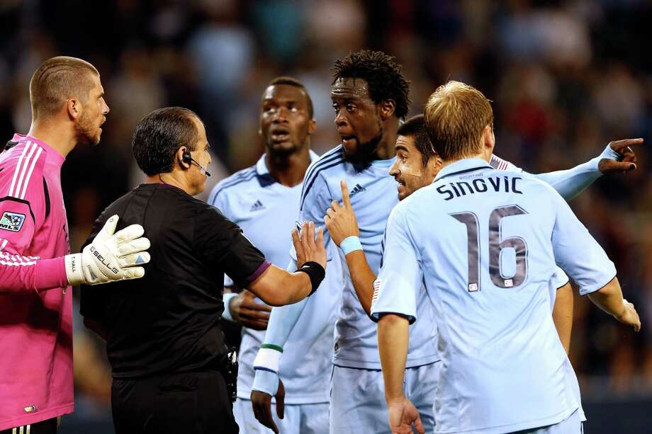 KANSAS CITY, KS - SEPTEMBER 14:  C.J. Sapong #17, Kei Kamara #23, Paulo Nagamura #6, and Seth Sinovic #16 of Sporting KC argue over a hand ball call with referee Baldomero Toledo as goalkeeper Tally Hall #1 of Houston Dynamo looks on during the MLS game at Livestrong Sporting Park on September 14, 2012 in Kansas City, Kansas. Photo: Jamie Squire, Getty Images / 2012 Getty Images