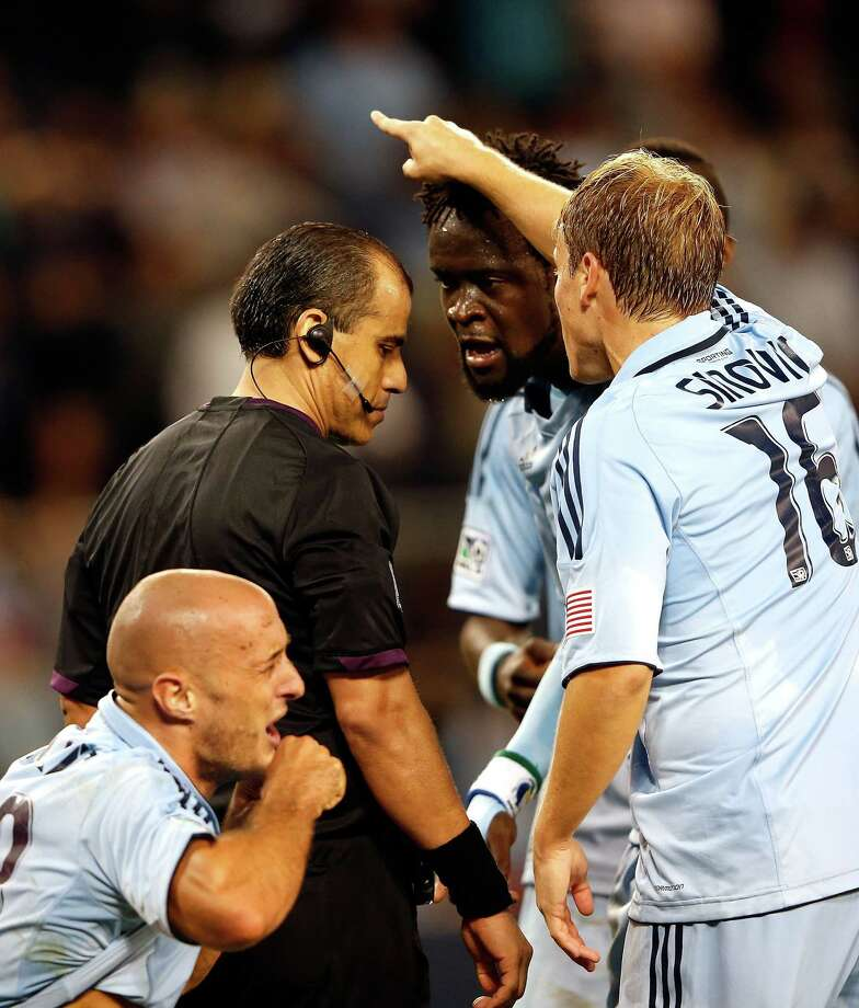 KANSAS CITY, KS - SEPTEMBER 14:  C.J. Sapong #17, Kei Kamara #23, Paulo Nagamura #6, and Seth Sinovic #16 of Sporting KC argue over a hand ball call with referee Baldomero Toledo during the MLS game against the Houston Dynamo at Livestrong Sporting Park on September 14, 2012 in Kansas City, Kansas. Photo: Jamie Squire, Getty Images / 2012 Getty Images