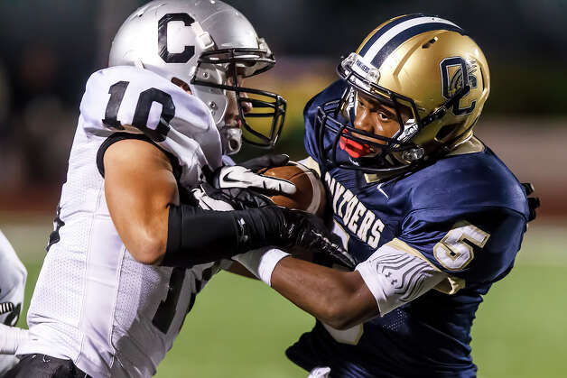 Clark's Samuel Carter (left) tries to strip the ball from O'Connor running back Tre Johnson during their game at Farris Stadium on Sept. 14, 2012.  Johnson ran for 325 yards and four touchdowns as O'Connor beat the Cougars 52-19 in their District 27-5A opener.  MARVIN PFEIFFER/ mpfeiffer@express-news.net Photo: MARVIN PFEIFFER, Express-News / Express-News 2012