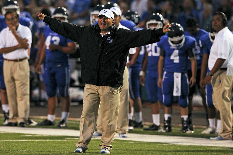 Unicorn head coach Chuck Caniford signals in to his team as Madison plays New Braunfels at New Braunfels Stadium on September 14, 2012. Photo: Tom Reel, Express-News / ©2012 San Antono Express-News