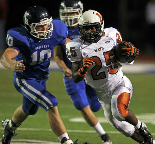 Maverick running back Galen McAllister slips by Marshal Lewis as Madison plays New Braunfels at New Braunfels Stadium on September 14, 2012. Photo: Tom Reel, Express-News / ©2012 San Antono Express-News