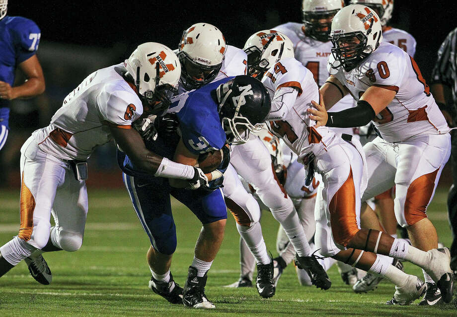 The Maverick defense swarms Cody Bevil as Madison plays New Braunfels at New Braunfels Stadium on September 14, 2012. Photo: Tom Reel, Express-News / ©2012 San Antono Express-News
